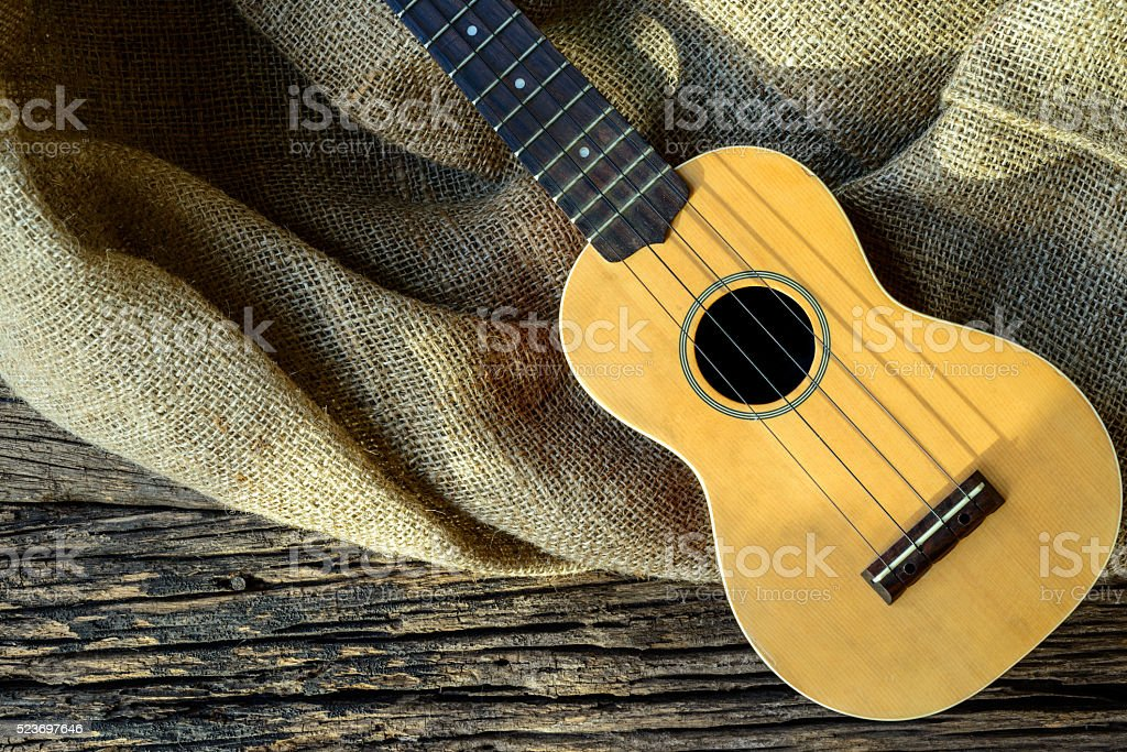 The Ukulele on a rustic table with sacking on wooden stock photo