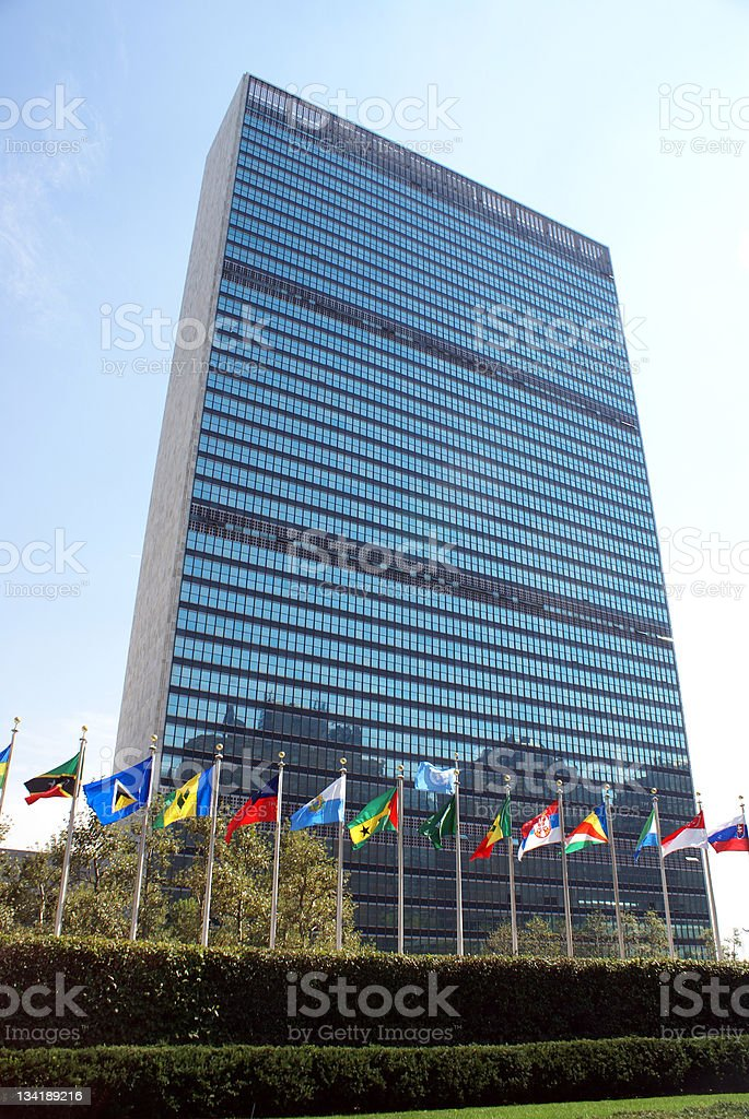 The United Nations building with various flags stock photo