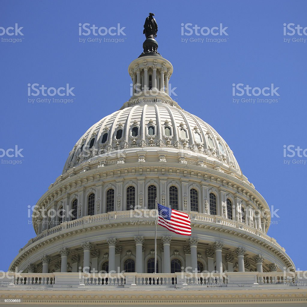 The United States Capitol dome and a raised flag royalty-free stock photo
