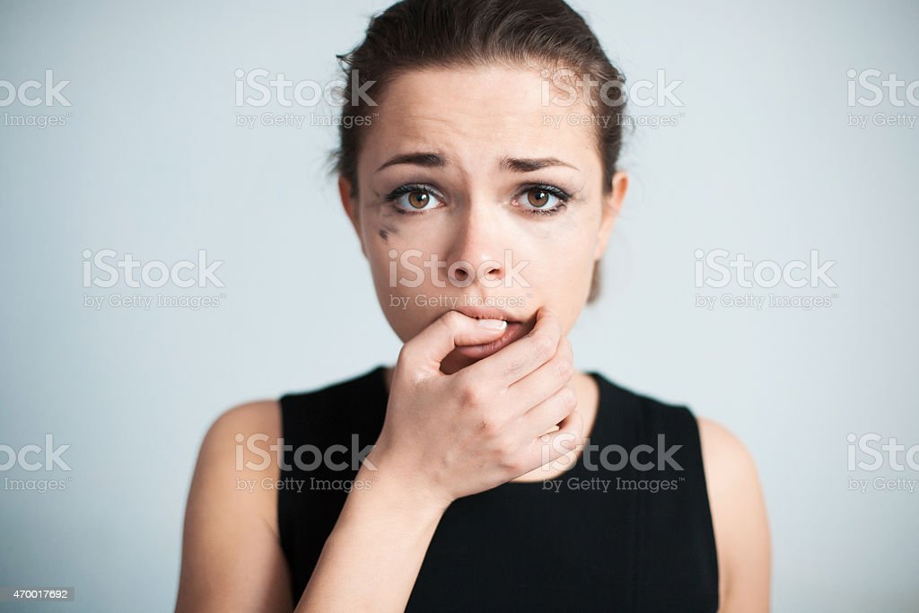 The upset woman bites one's nails stock photo