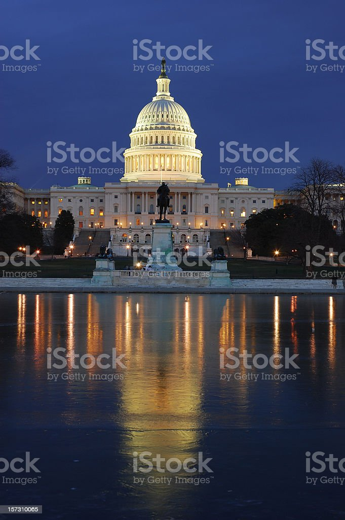 The U.S. Capitol lit up at night over water with reflection stock photo