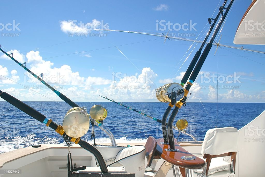 The view of a back of a boat with fishing rods off the back royalty-free stock photo