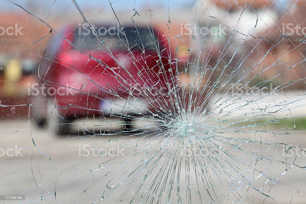 The view of a red car blurred through broken glass  stock photo