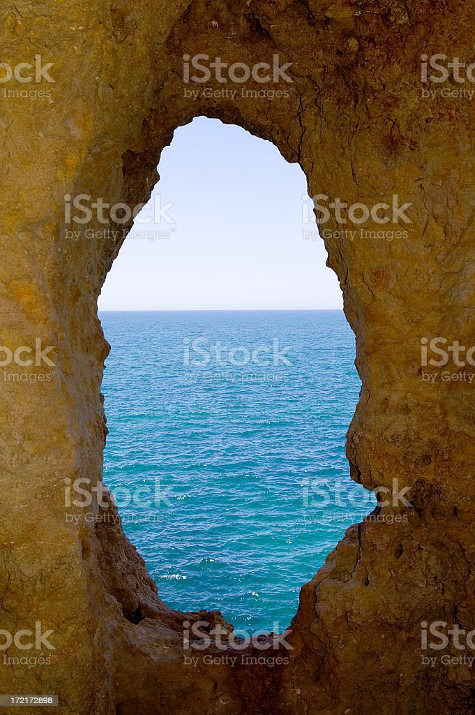 The view through a hole in the rock of the ocean stock photo