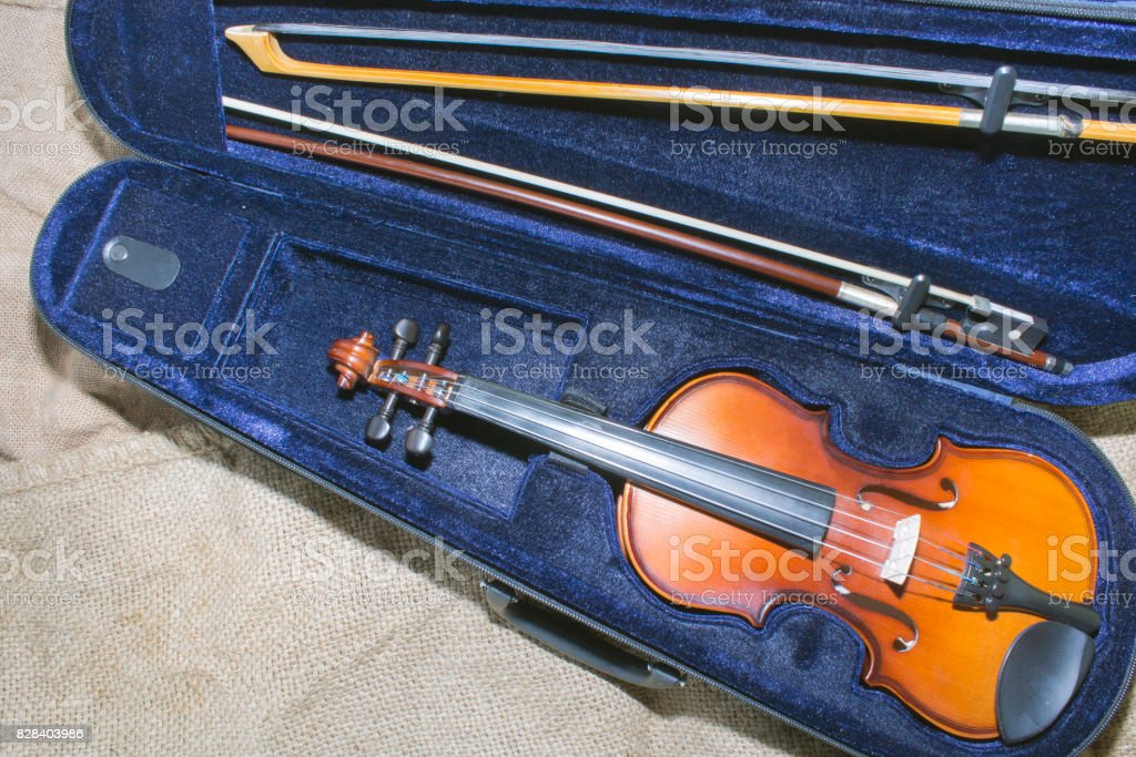 the violin in its case on the background of old sacking. stock photo