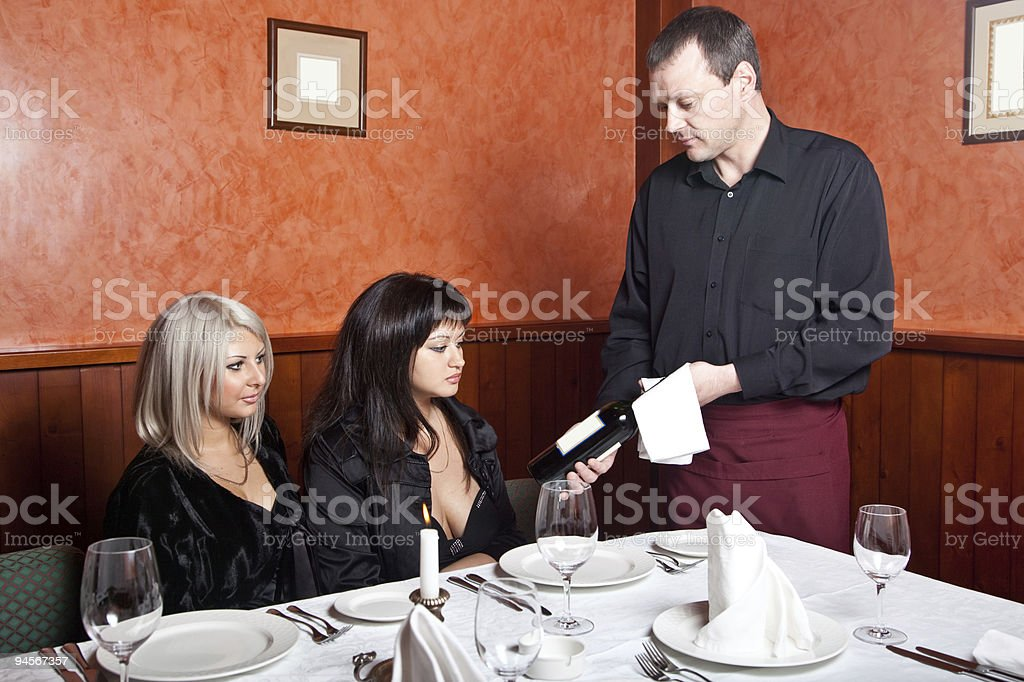 The waiter shows a bottle of wine visitors stock photo