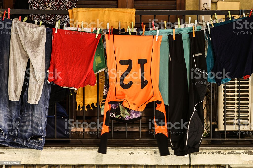 The washing hanged out of a balcony with a sport shirt stock photo