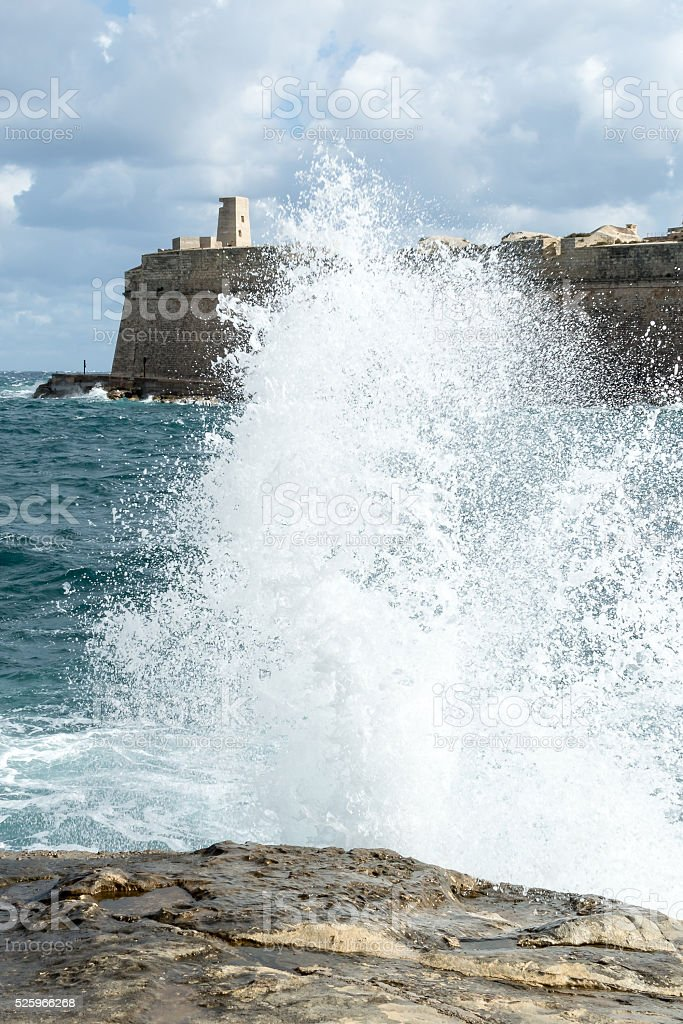 The waves beat against the rocky shore in Malta stock photo