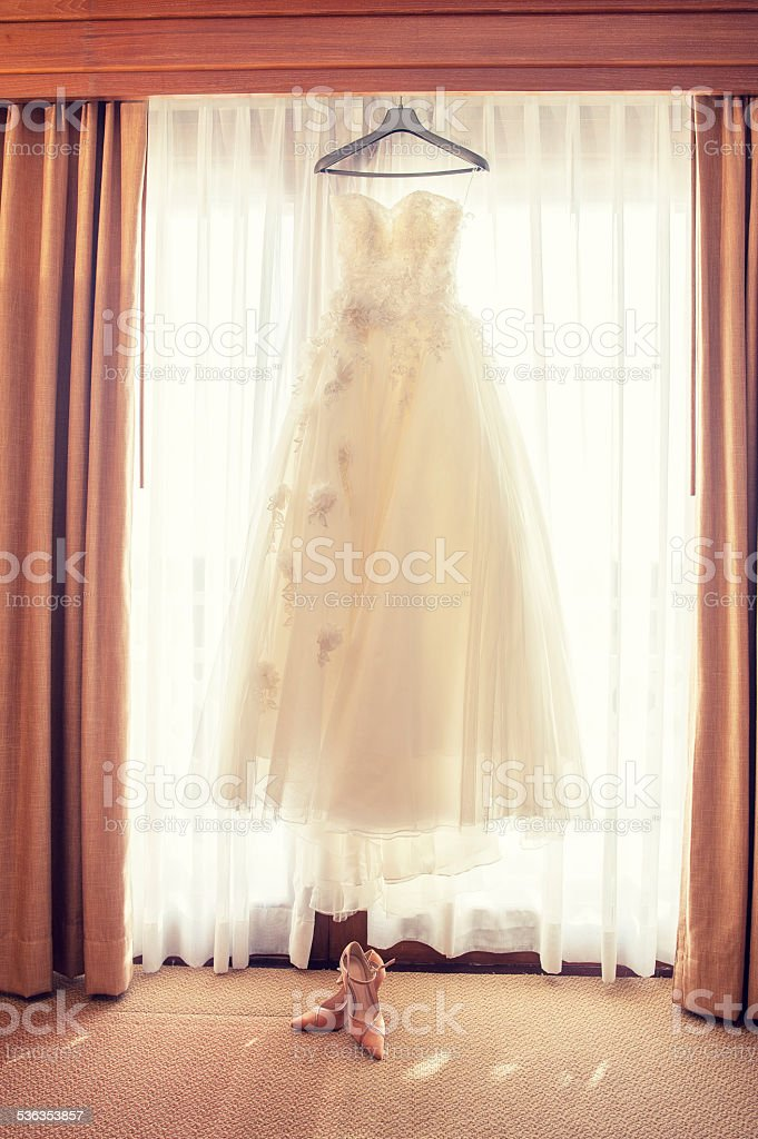 The Wedding Dress hanging at the window stock photo
