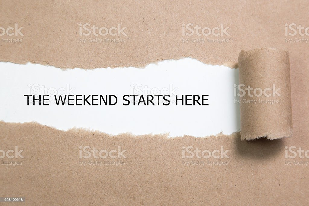 The Weekend Starts Here word written under torn paper. stock photo