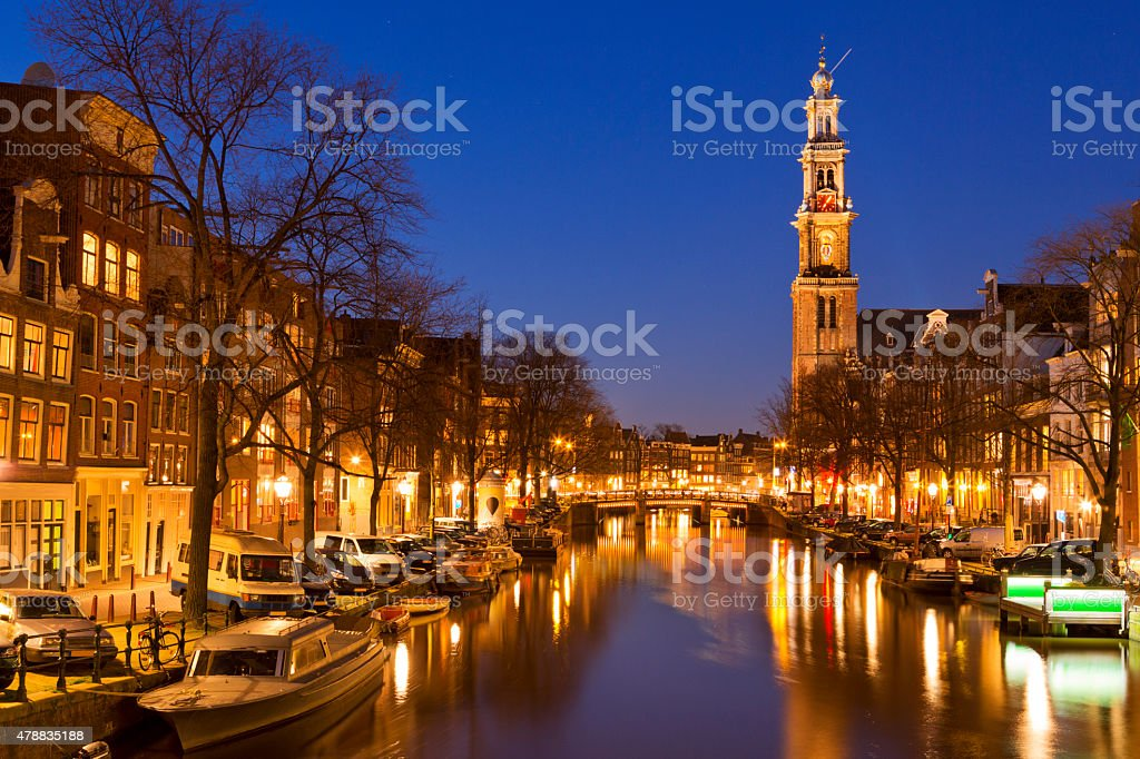 The Western Church and a canal in Amsterdam at night stock photo