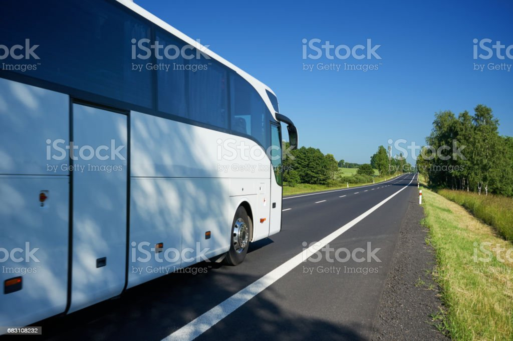 The white bus traveling on asphalt road in a landscape stock photo
