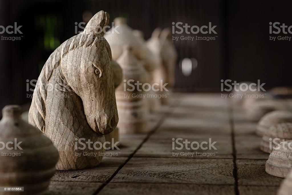 The White knight on the wood chess board. stock photo