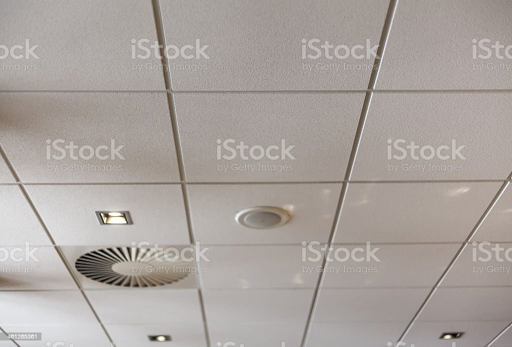 The white tiles of an office ceiling stock photo