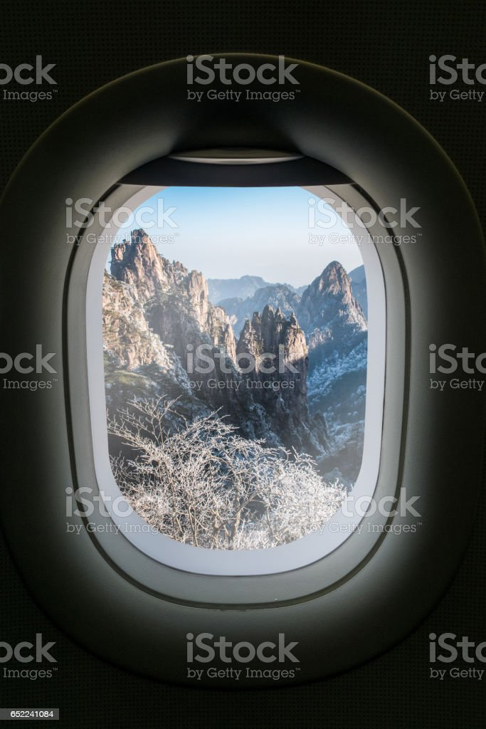 The window of airplane with travel destination attraction. Huangsan mountain range, China stock photo
