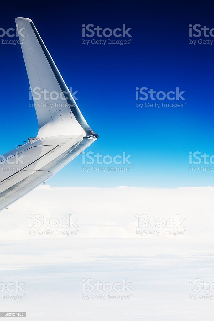 The wing of an airplane flying in the sky stock photo