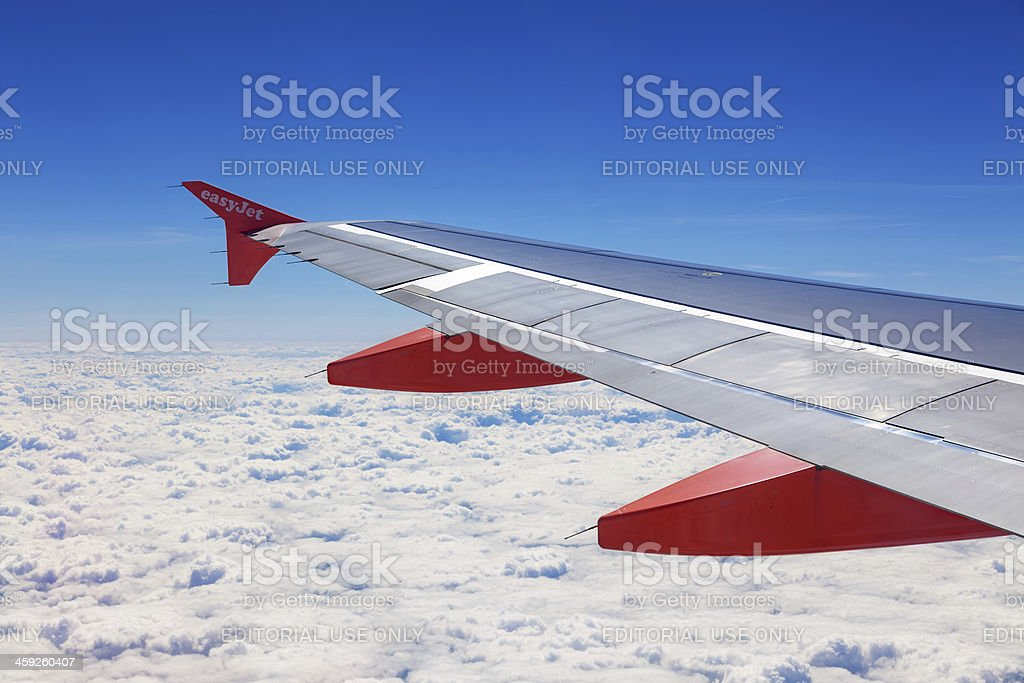 The wing of an EasyJet aircraft above white clouds royalty-free stock photo