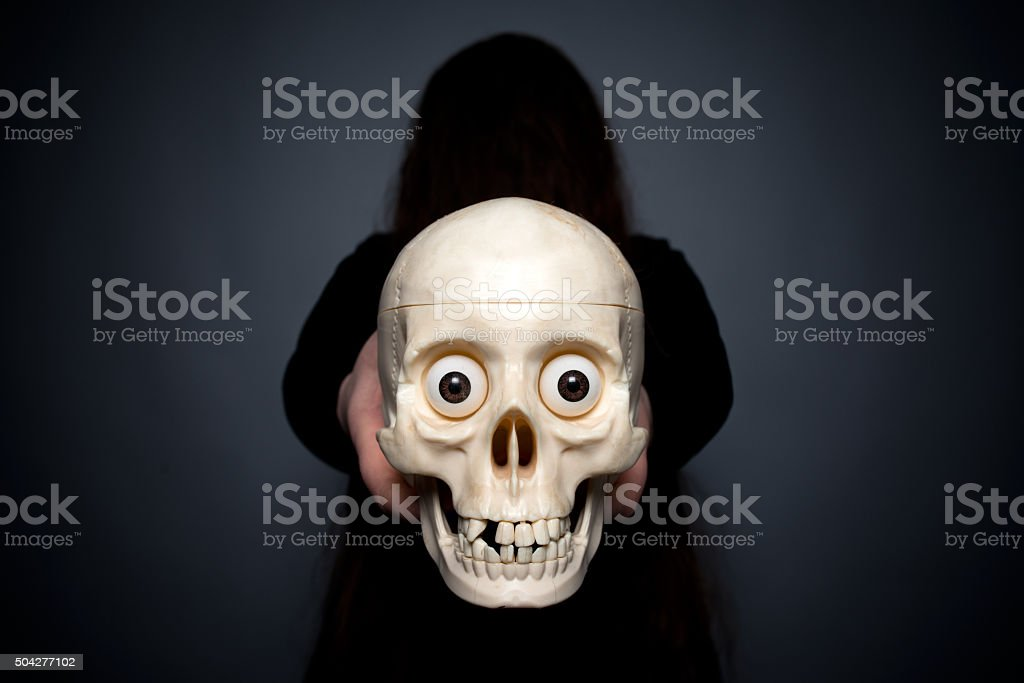 the witch holds a skull in hand stock photo