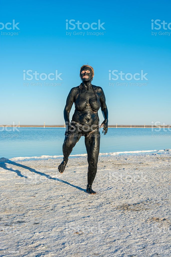 The woman accepts the curative mud baths on the lake Baskunchak. stock photo