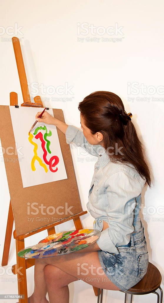 The woman artist and its painting stock photo