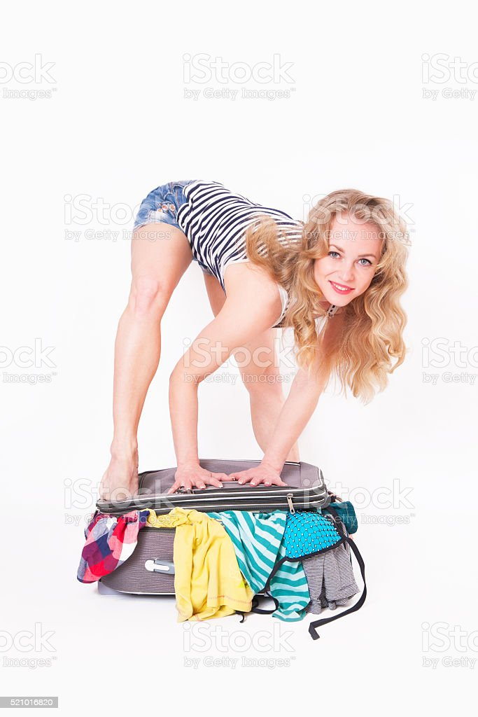 The woman closes a suitcase full of clothes stock photo