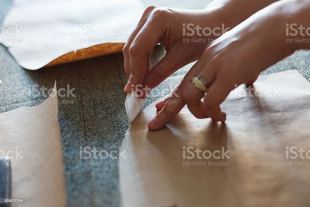 The woman draws with soap markup patterns on tweed fabric stock photo