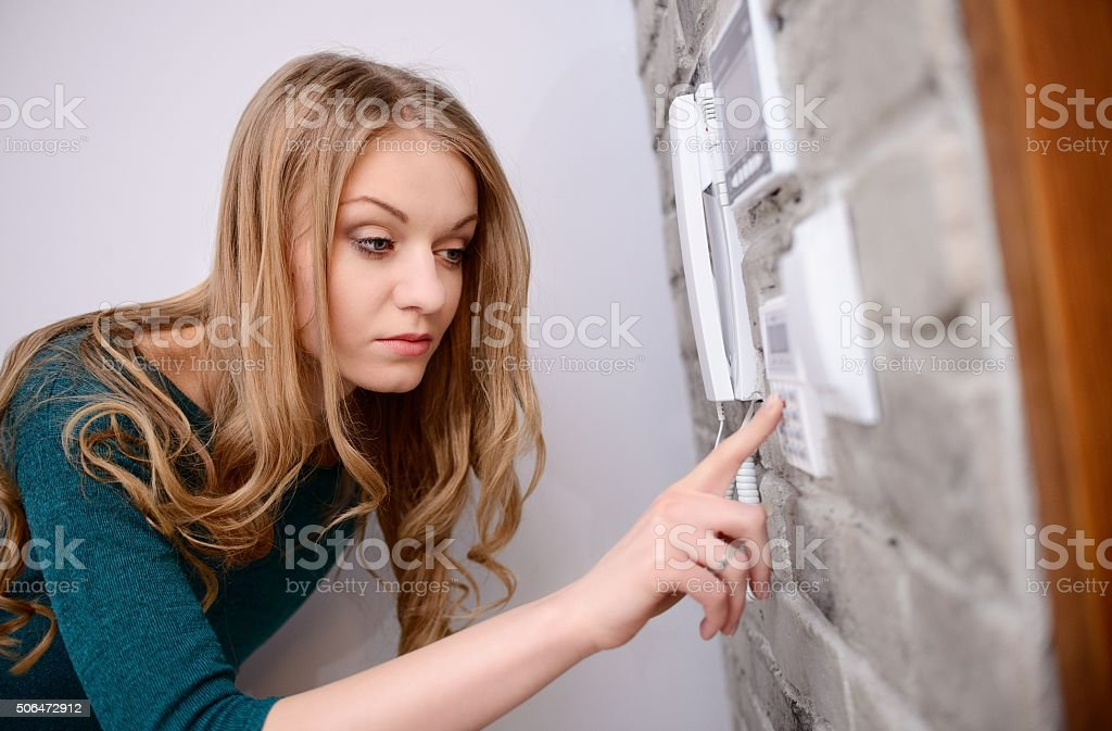 The woman entering code into the keypad stock photo