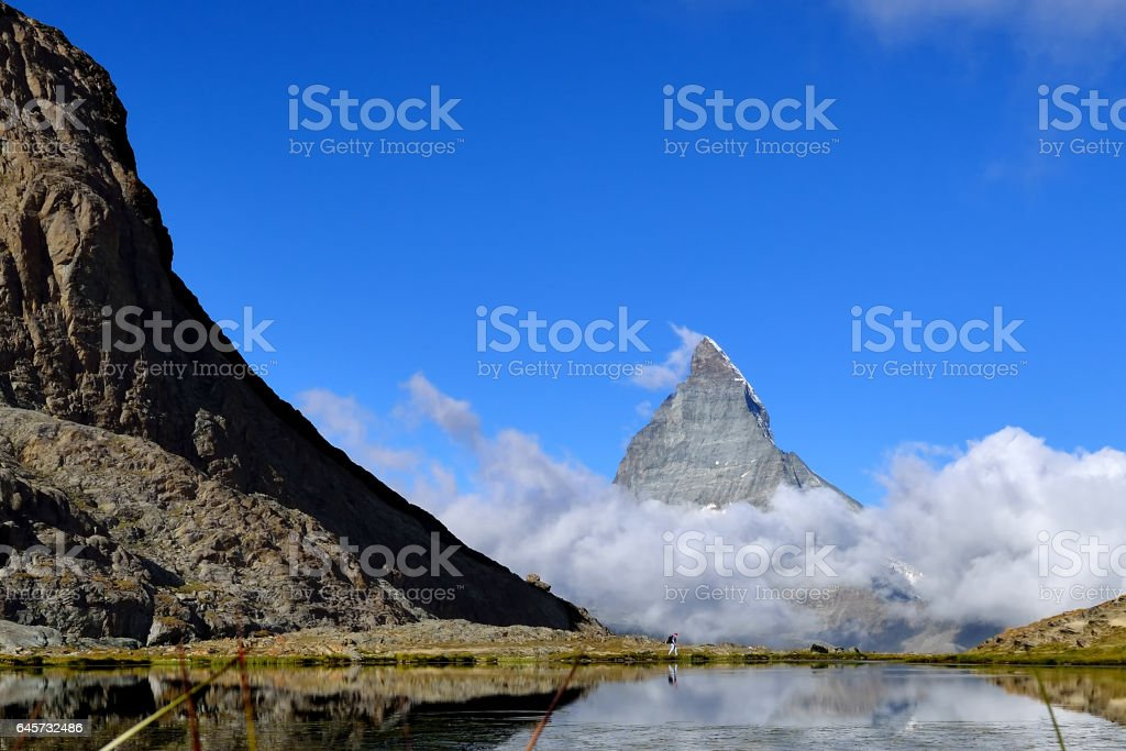 The woman hiking to Riffelsee lake in front of Matterhorn and cloud during summer, Zermatt Switzerland stock photo