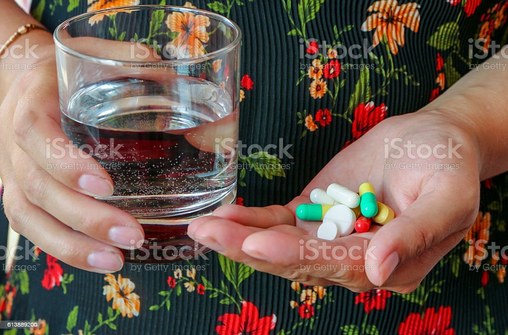 The woman holds the pills and a glass of water. stock photo
