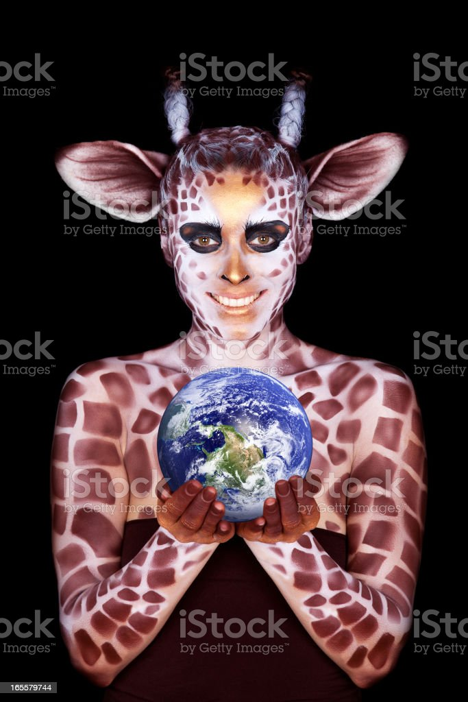 The woman in an image of a giraffe, holds globe royalty-free stock photo