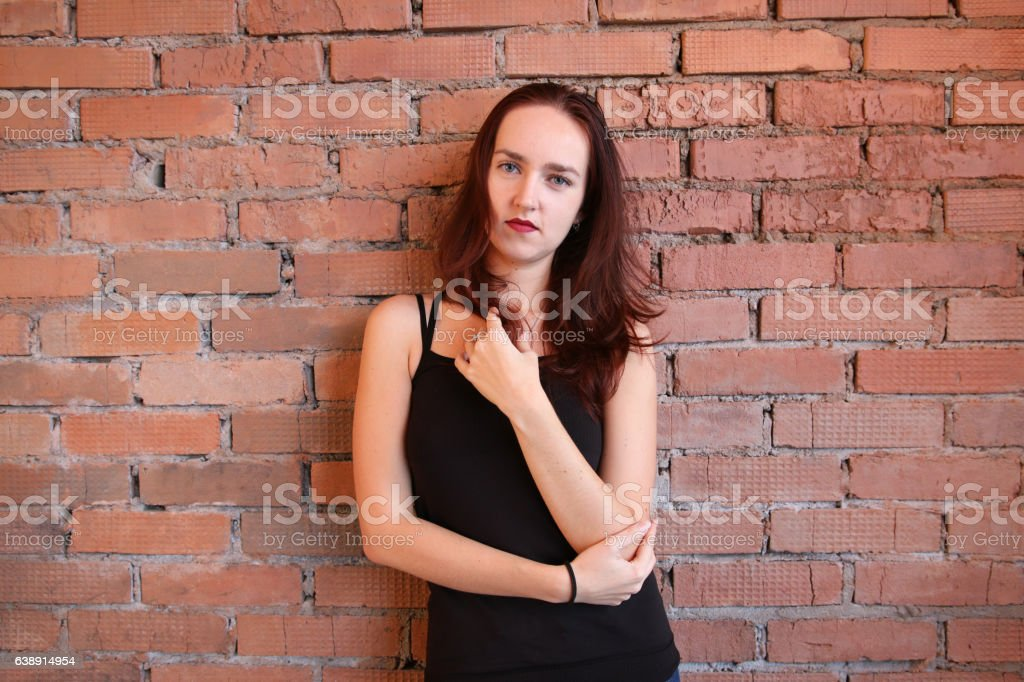 The woman in black top poses near a brick wall stock photo