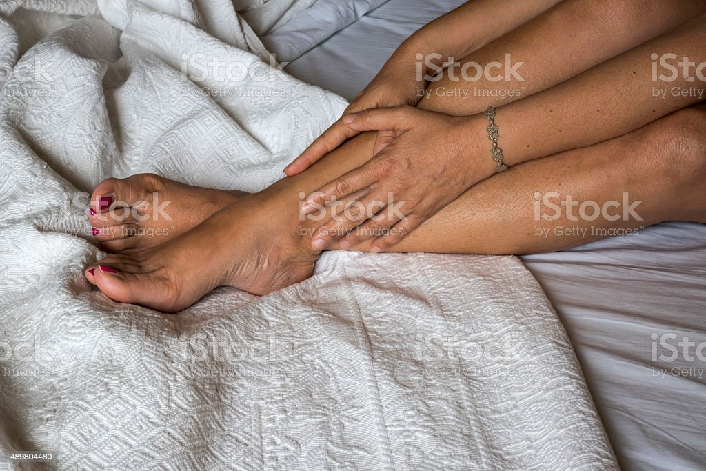 The woman massaging her legs on a bed stock photo