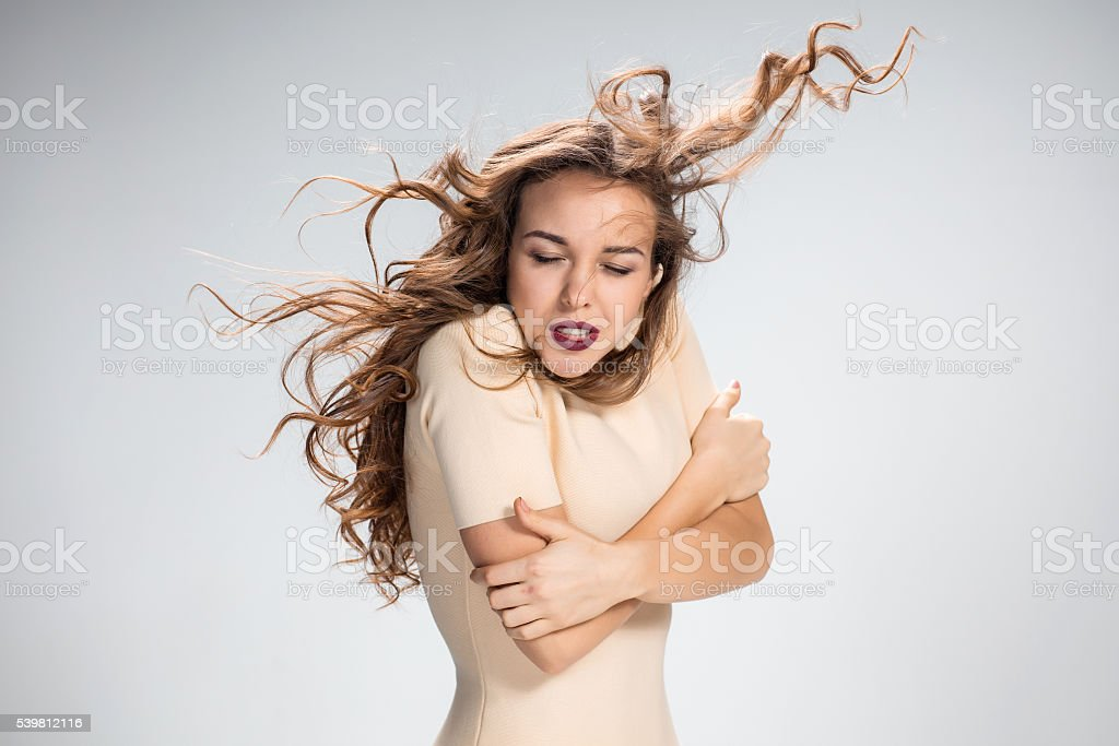 The woman with hair blowing in the wind on gray stock photo