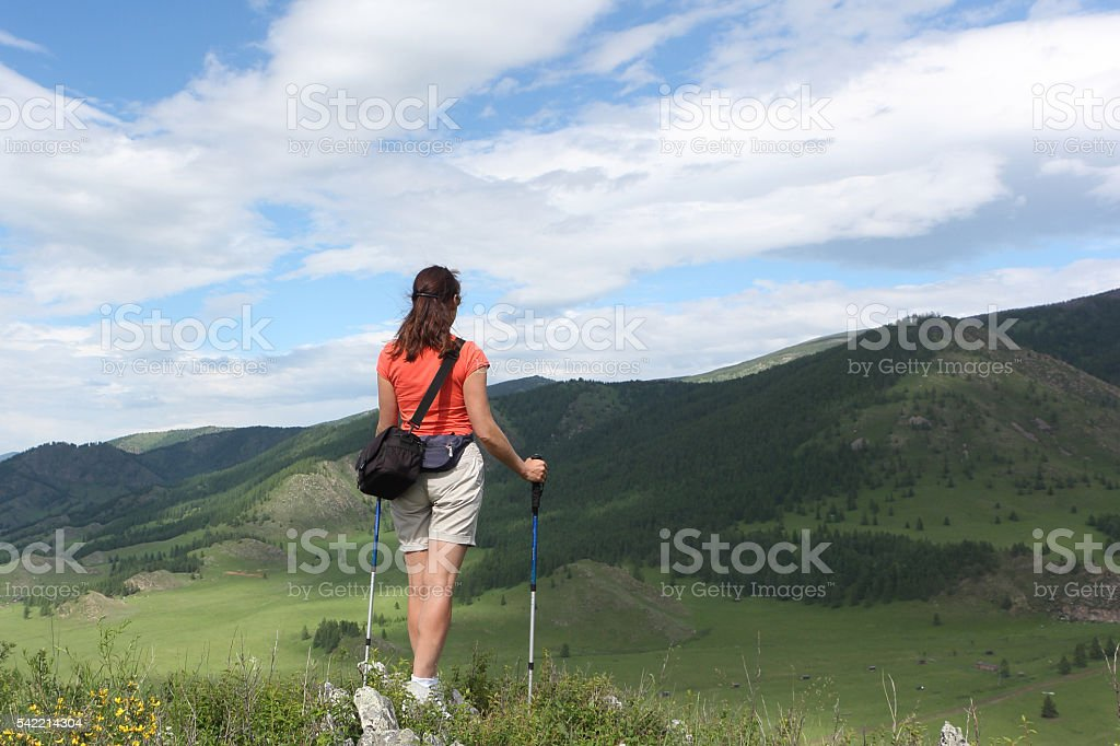 The woman with long hair standing on mountain top with sticks stock photo