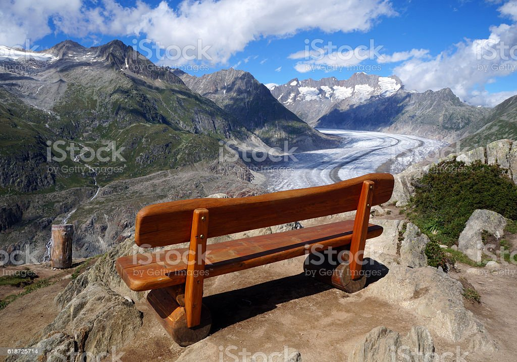 The wooden bench above the Aletsch glacier in the Swiss Alps stock photo