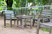 The wooden chairs with wooden table colorful in the garden.