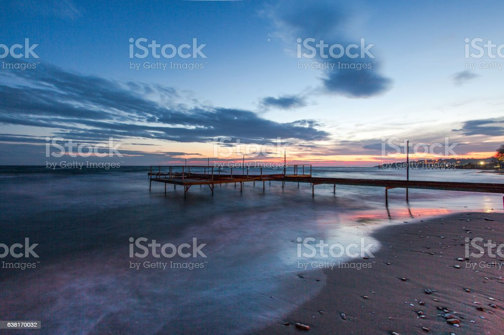The wooden Jetty with beautiful, vibrant pink and Purple Sunset stock photo