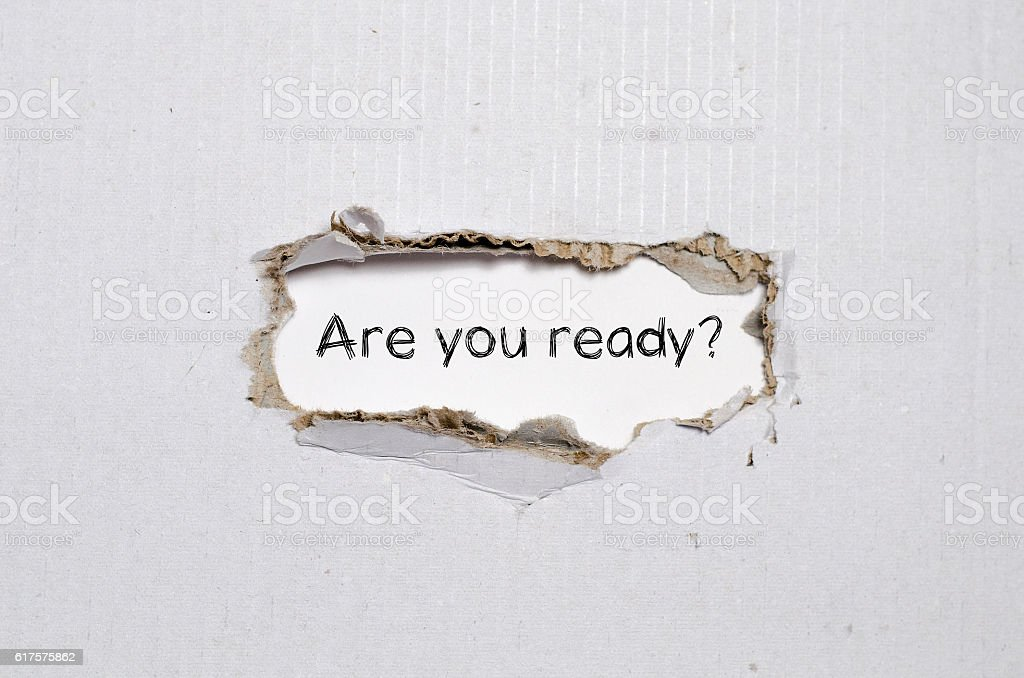 The word are you ready appearing behind torn paper. stock photo