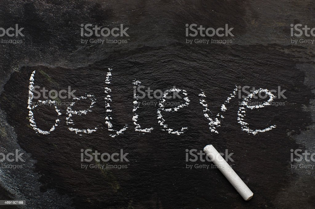 The word BELIEVE written with chalk on black stone stock photo