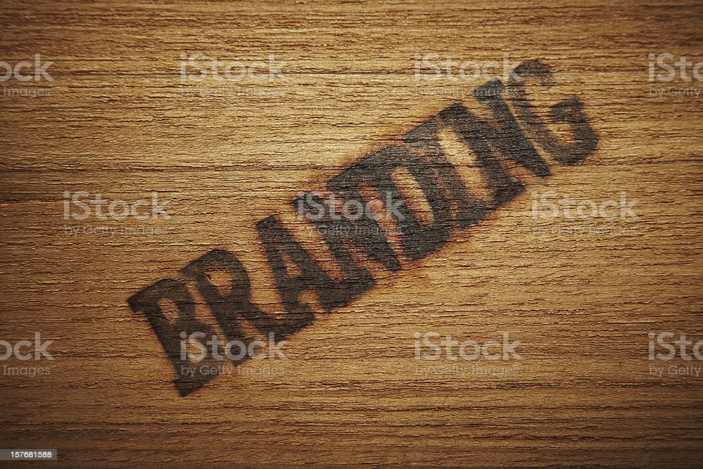 The word branding stamped diagonally on a wooden background royalty-free stock photo