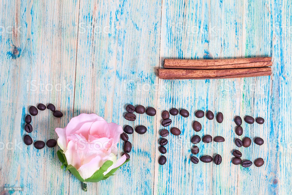 The word Coffee spelled with coffee beans on wood. stock photo