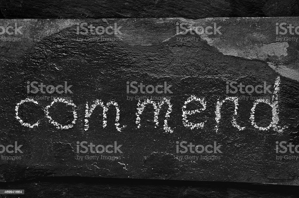 The word COMMEND written with chalk on black stone. stock photo