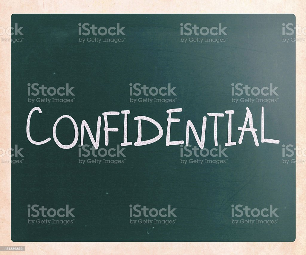 The word 'Confidential' handwritten with white chalk on a blackb stock photo
