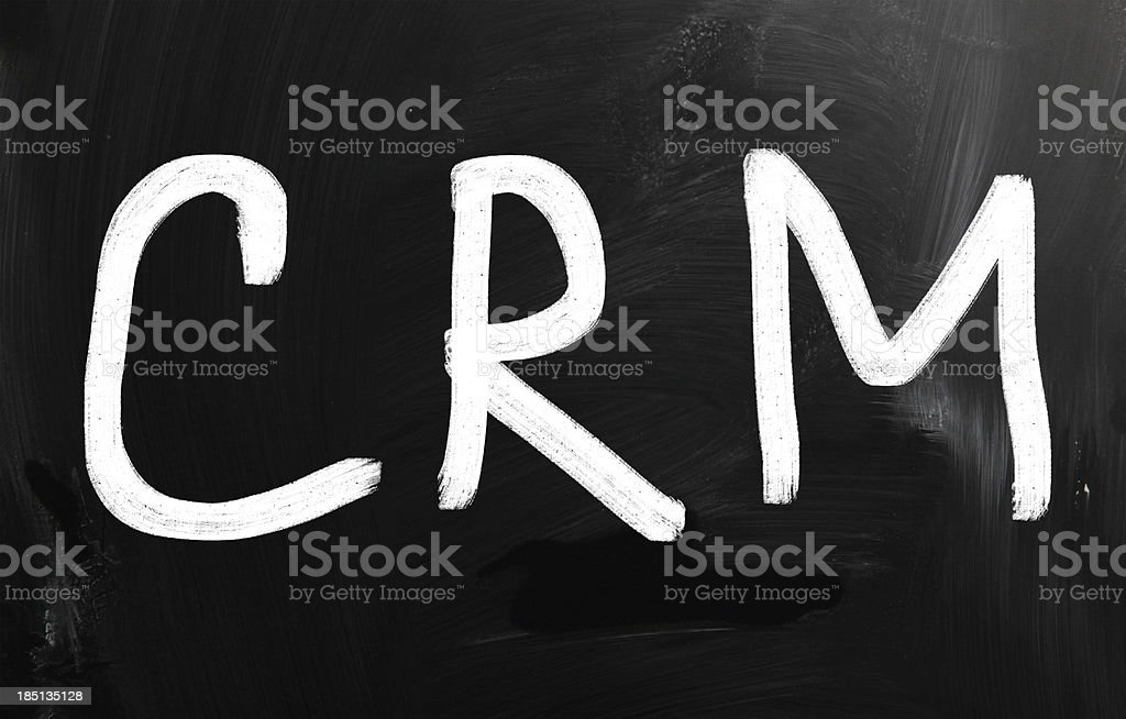 The word 'CRM' handwritten with white chalk on a blackboard royalty-free stock photo