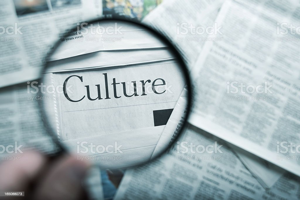 The word culture magnified on newspapers royalty-free stock photo