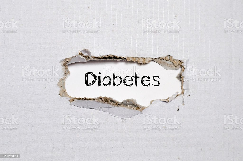 The word diabetes appearing behind torn paper. stock photo
