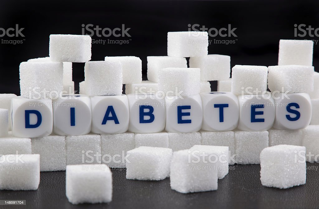 The word diabetes spelled on dice placed among sugar cubes stock photo