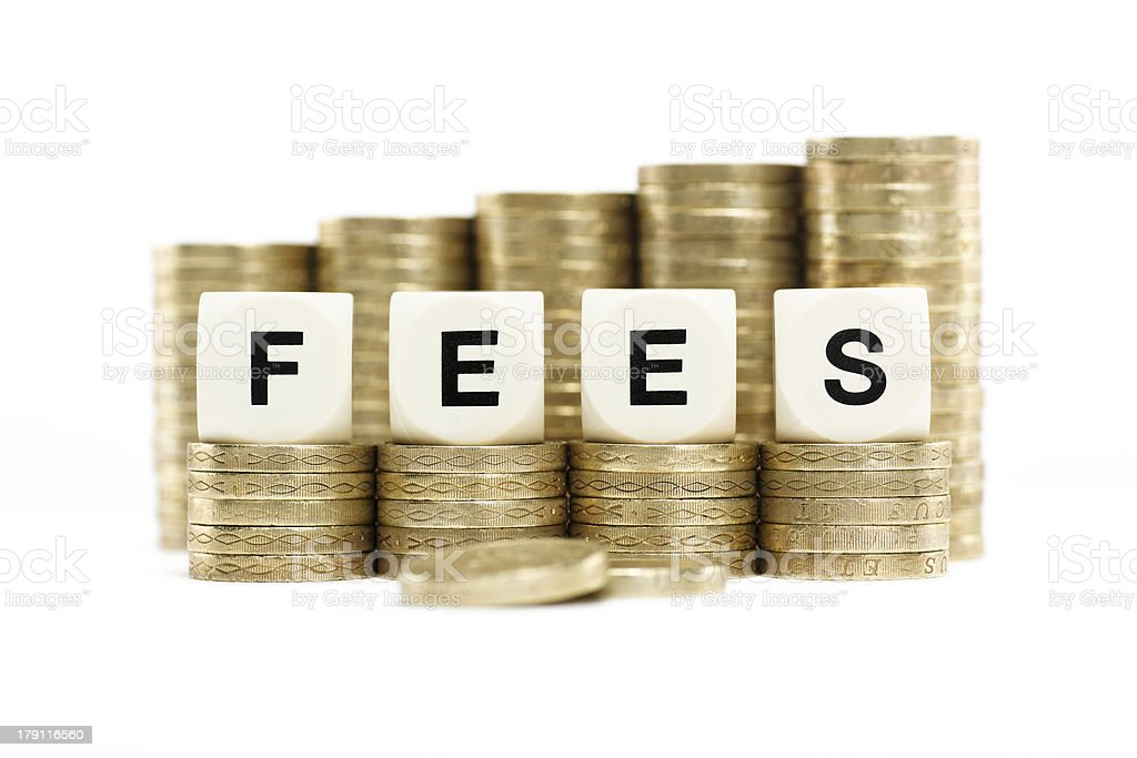 The word FEES on gold coin stacks with white background royalty-free stock photo