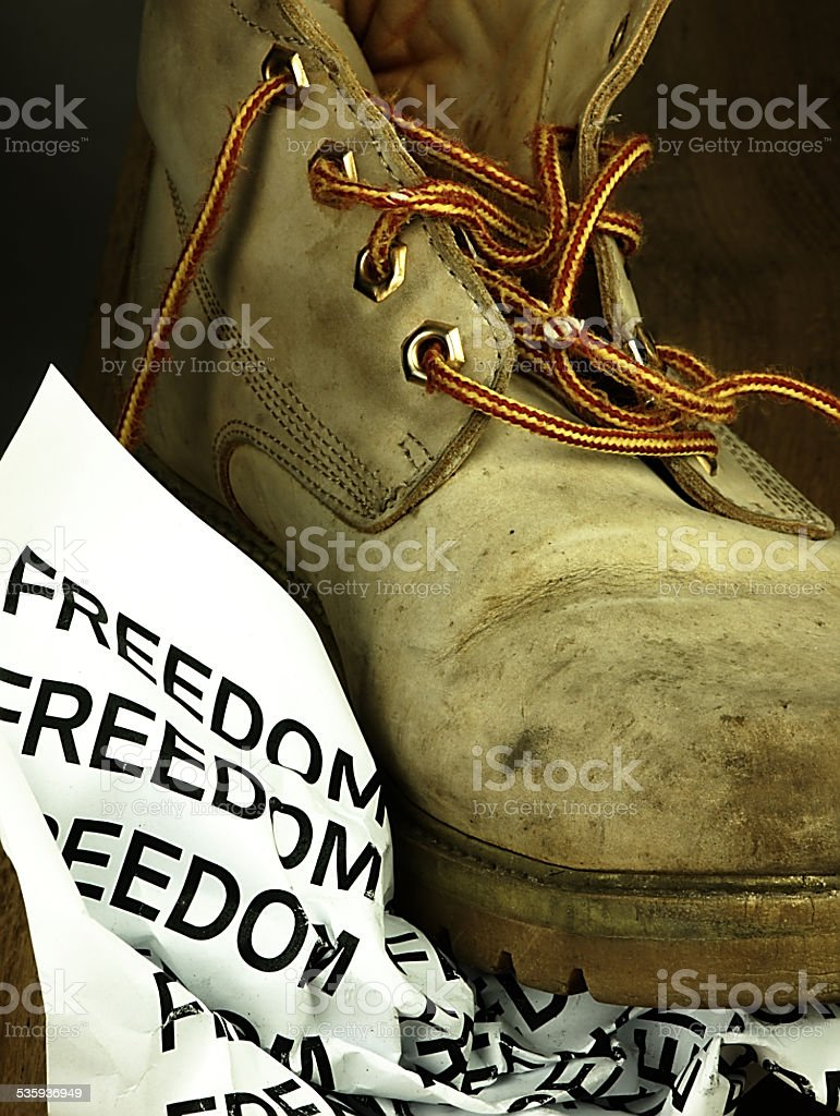 The word freedom crushed by a heavy, old military boot. stock photo