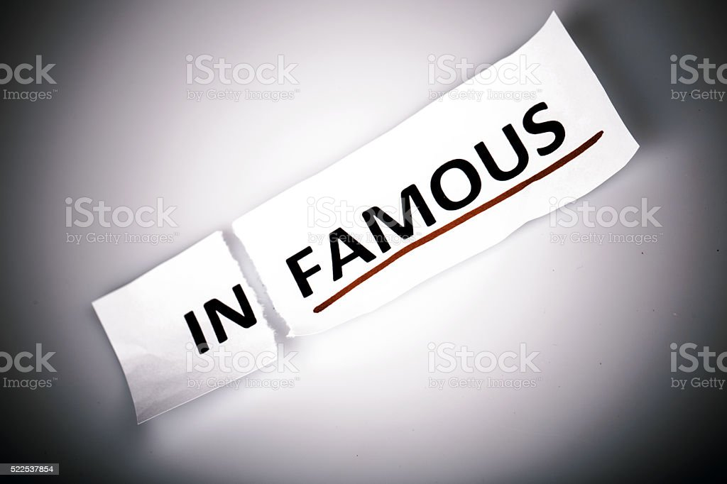 The word infamous changed to famous on torn paper stock photo